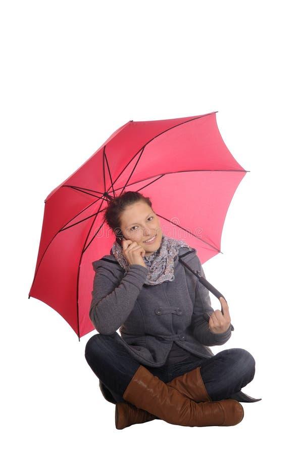Donna con il telefono mobile e l'ombrello fotografie stock libere da diritti