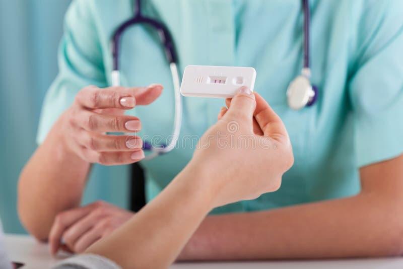 Donna con il test di gravidanza ed il ginecologo fotografia stock libera da diritti