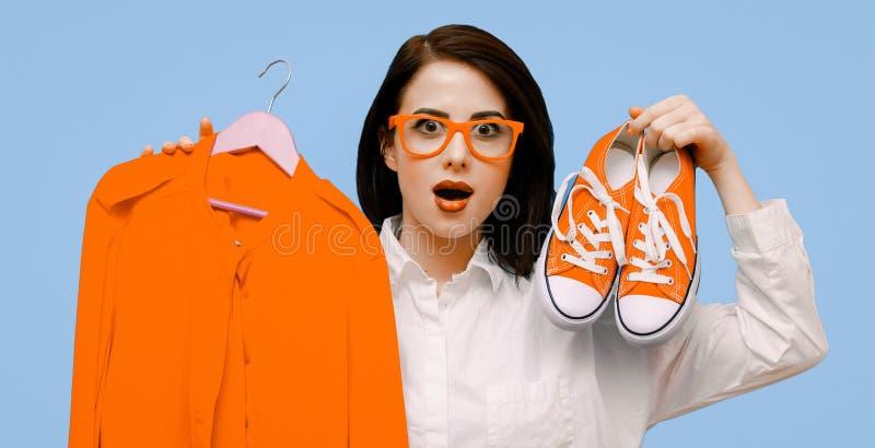 Donna con il vestito ed i gumshoes che stanno sul backgroand blu fotografia stock