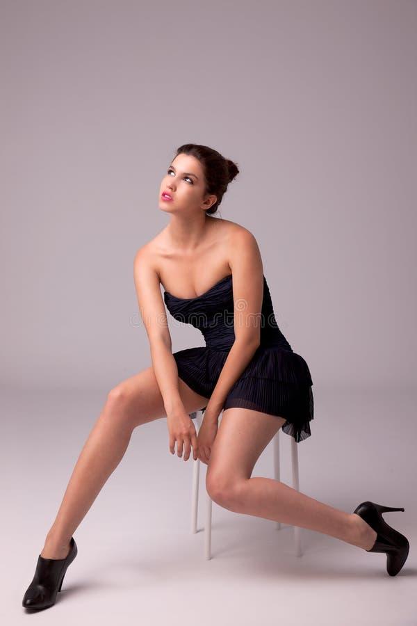 Donna con il vestito elegante che osserva in su al ligh fotografia stock libera da diritti