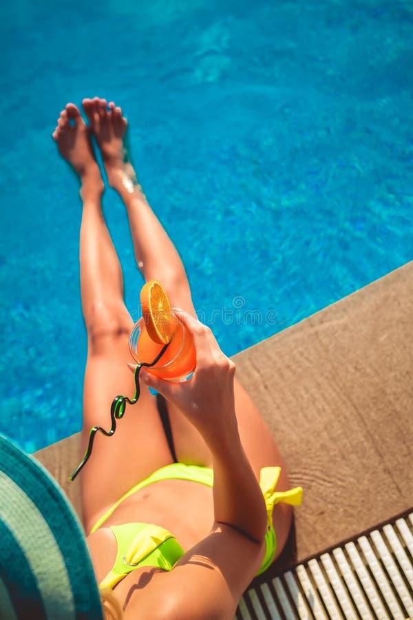 Donna con il vetro di cocktail che raffredda nel sole tropicale vicino alla piscina immagini stock libere da diritti