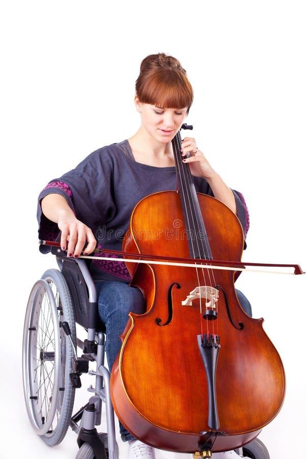 Donna con il violoncello sulla sedia a rotelle immagini stock libere da diritti