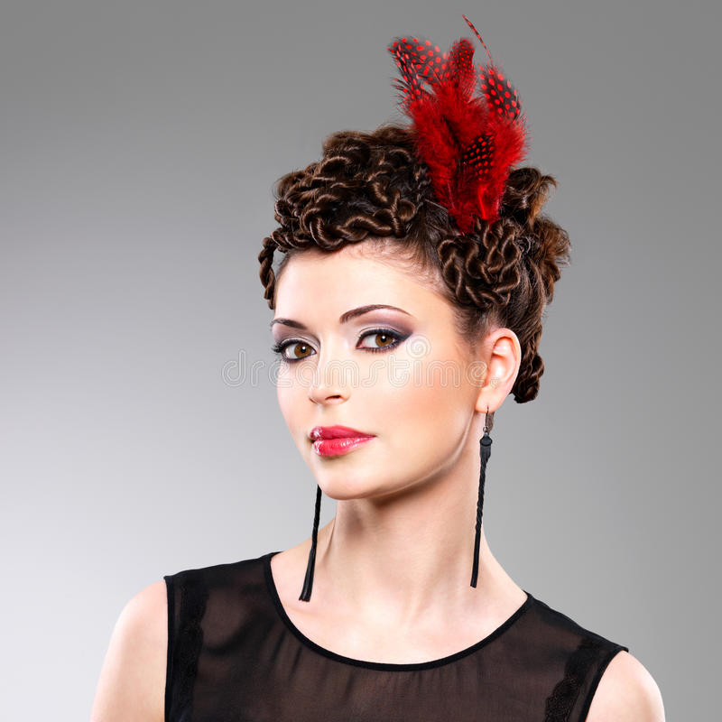 Donna con l'acconciatura di modo con la piuma rossa in capelli fotografie stock libere da diritti