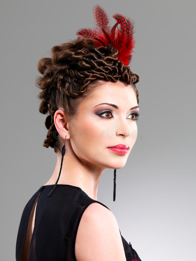 Donna con l 39 acconciatura di modo con la piuma rossa in for Modo 10 prezzi