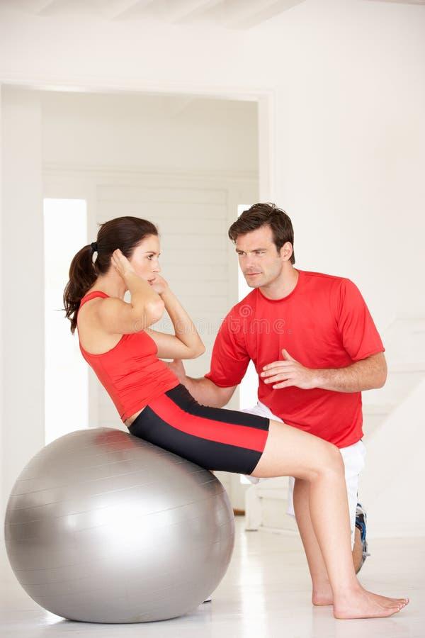 Donna con l'addestratore personale in ginnastica domestica fotografia stock
