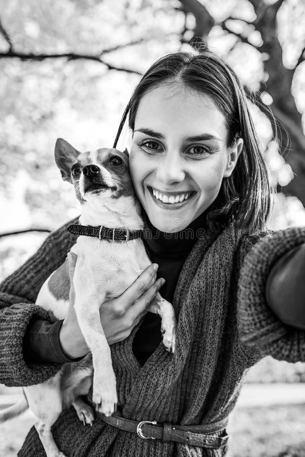 Donna con l'aria aperta del cane in autunno che fa selfie fotografia stock libera da diritti