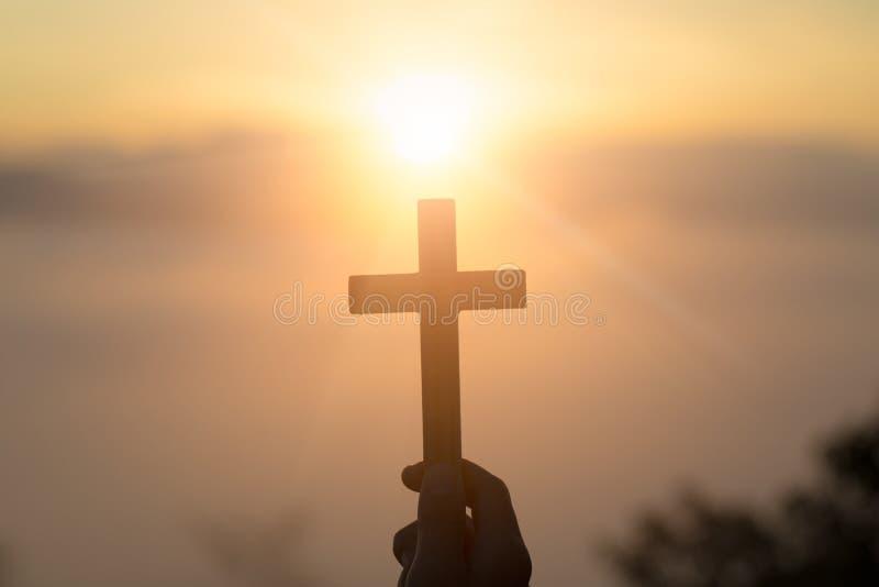 Donna con l'incrocio di legno in mani che prega per la benedizione dal dio sul fondo di luce solare, concetto di speranza - immag fotografia stock