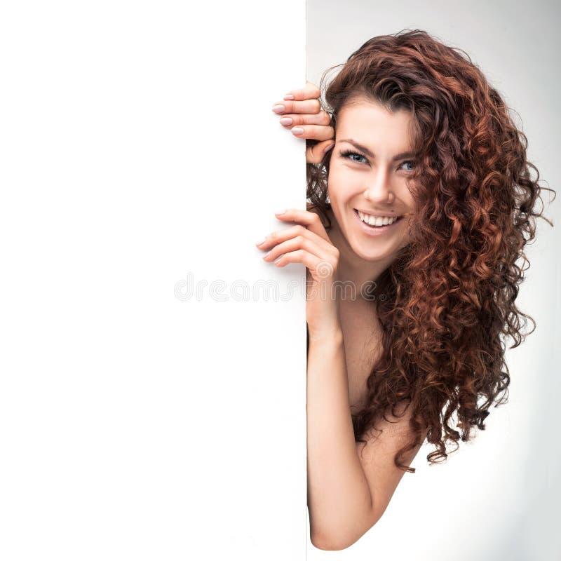 Donna con l'insegna marrone della tenuta dei capelli ricci fotografie stock libere da diritti