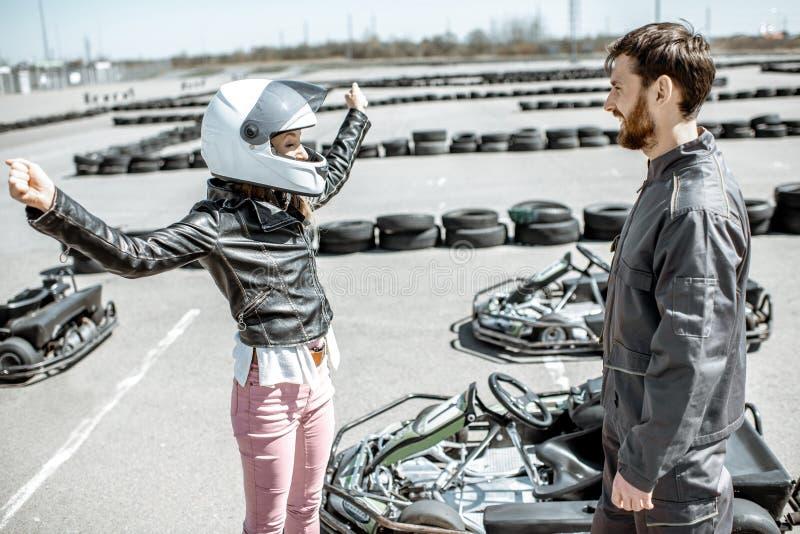 Donna con l'istruttore sulla pista da go-kart fotografie stock