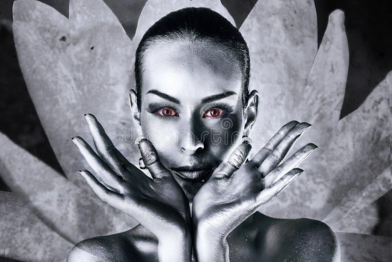 Donna con l'occhi rossi in un fiore di loto immagini stock