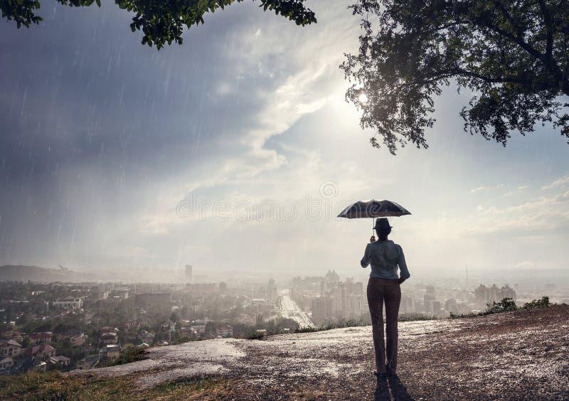 Donna con l'ombrello ed il paesaggio urbano fotografia stock libera da diritti