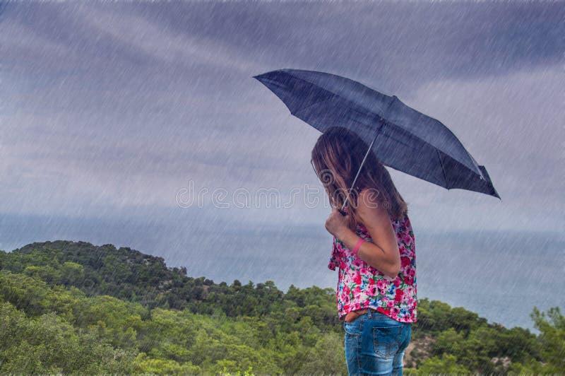 Donna con l'ombrello nella pioggia immagini stock libere da diritti