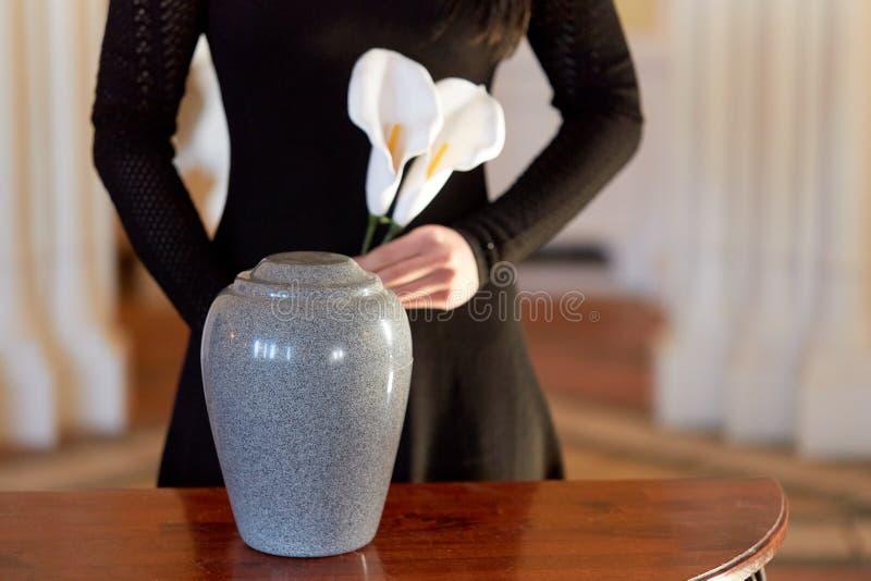 Donna con l'urna di cremazione al funerale in chiesa fotografie stock
