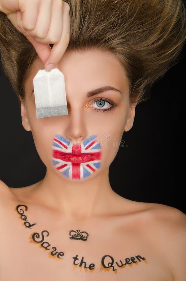 Donna con la bandiera di inglese sulla bustina di tè e del fronte fotografia stock