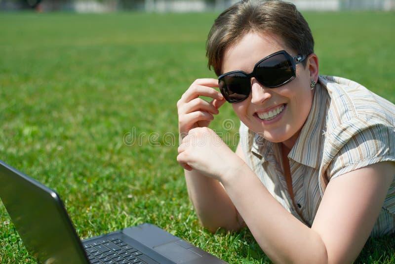 Donna con la bugia del taccuino su erba verde fotografia stock libera da diritti