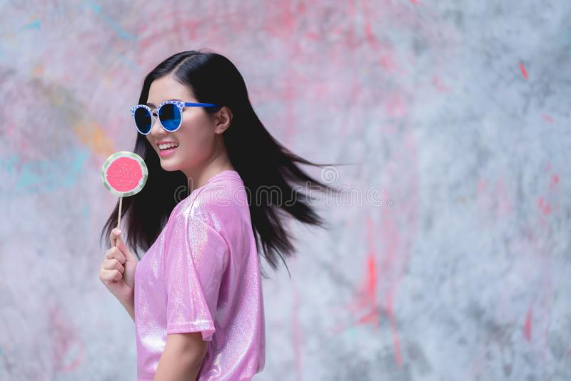 Donna con la caramella della lecca-lecca che porta il vestito rosa da modo su variopinto immagini stock