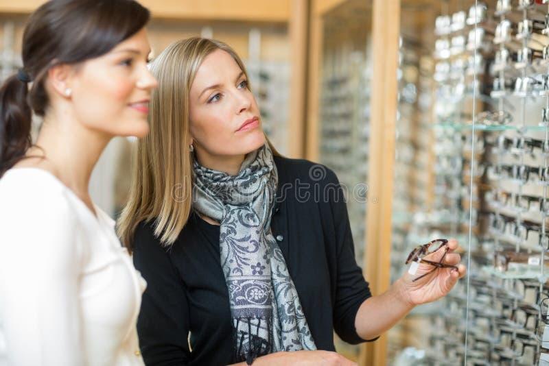 Donna con la commessa che seleziona gli occhiali immagine stock