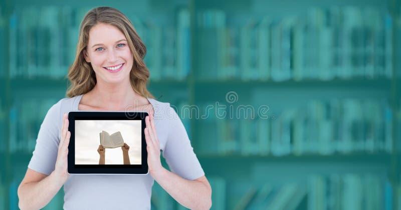 Donna con la compressa che mostra le mani con il libro contro lo scaffale per libri confuso con la sovrapposizione dell'alzavola immagini stock