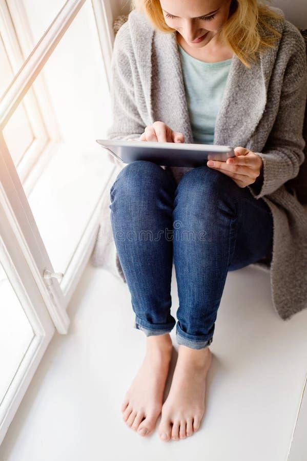 Donna con la compressa che si siede sul davanzale della finestra, giorno soleggiato immagine stock libera da diritti