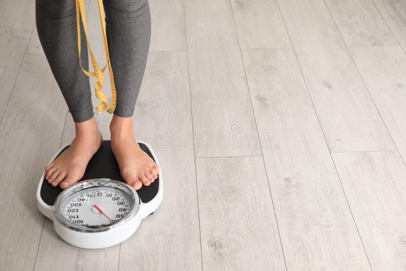 Donna con la condizione del nastro sulle scale all'interno Problema di peso eccessivo immagini stock