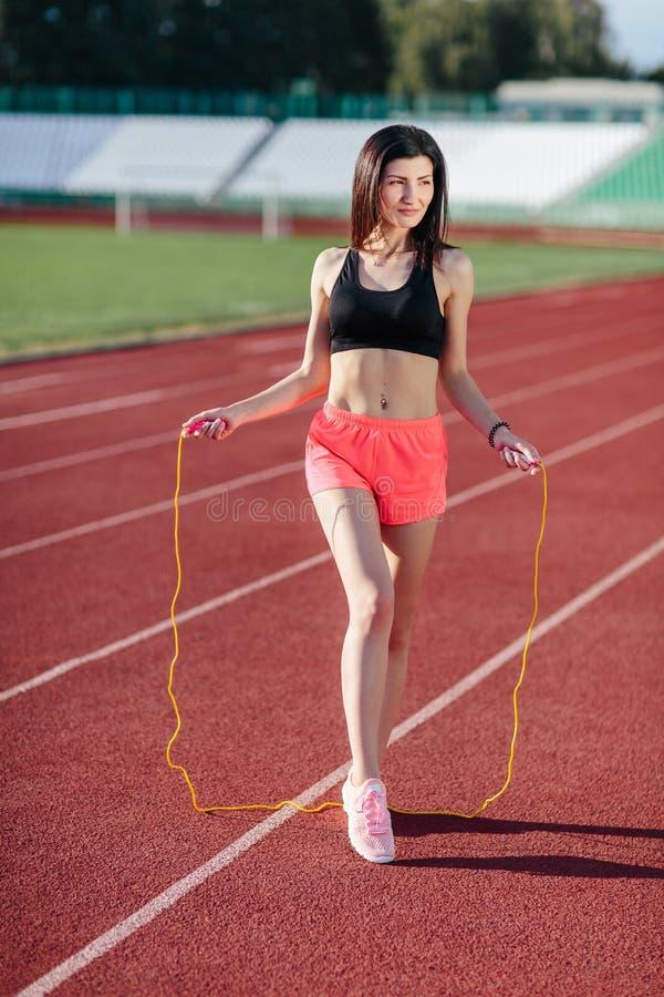 Donna con la corda Donna castana di sport che posa con la corda gialla, attività sana Donna sexy con il salto della corda Donna m fotografie stock