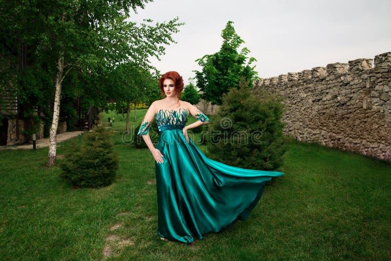 Donna con la corona sulla testa in vestito lungo verde che posa sguardo da parteggiare fotografia stock libera da diritti