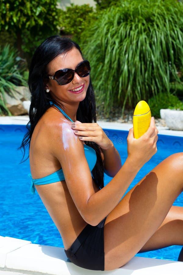 Donna con la crema del sole dal raggruppamento fotografie stock libere da diritti