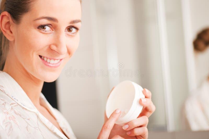 Donna con la crema di fronte immagine stock libera da diritti