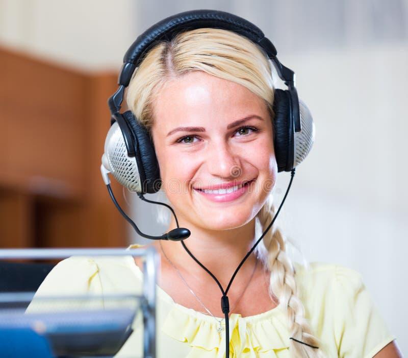 Donna con la cuffia avricolare che funziona al call-center fotografia stock