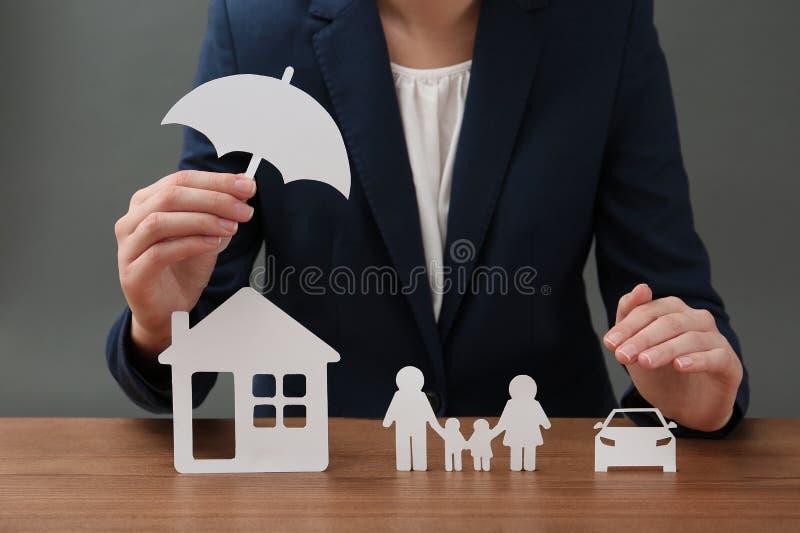 Donna con la famiglia, la casa, l'automobile e l'ombrello della carta del ritaglio alla tavola, primo piano fotografie stock libere da diritti
