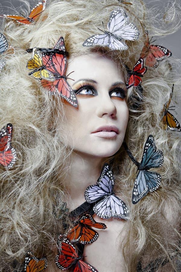 Donna con la farfalla in capelli ricci. immagini stock