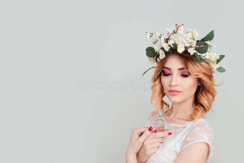 Donna con la fascia dei fiori della fascia con la bottiglia di profumo immagini stock libere da diritti