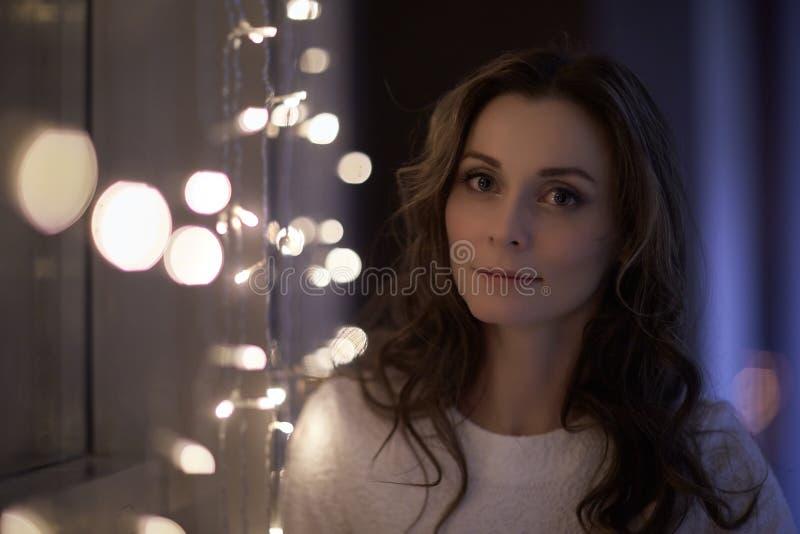 Donna con la ghirlanda della luce di Natale immagine stock