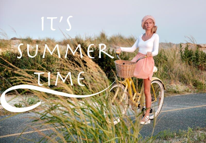 Donna con la guida della bicicletta sulla spiaggia divertendosi e sorridendo fotografie stock libere da diritti