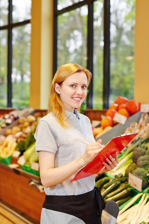 Donna con la lavagna per appunti nel supermarkt fotografia stock