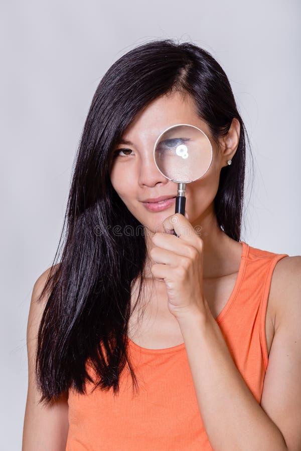 Donna con la lente d'ingrandimento fotografia stock libera da diritti