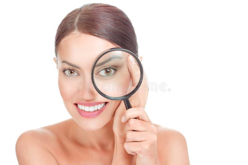 Donna con la lente d'ingrandimento vicino alle grinze del mimo dell'occhio sul suo fronte fotografie stock