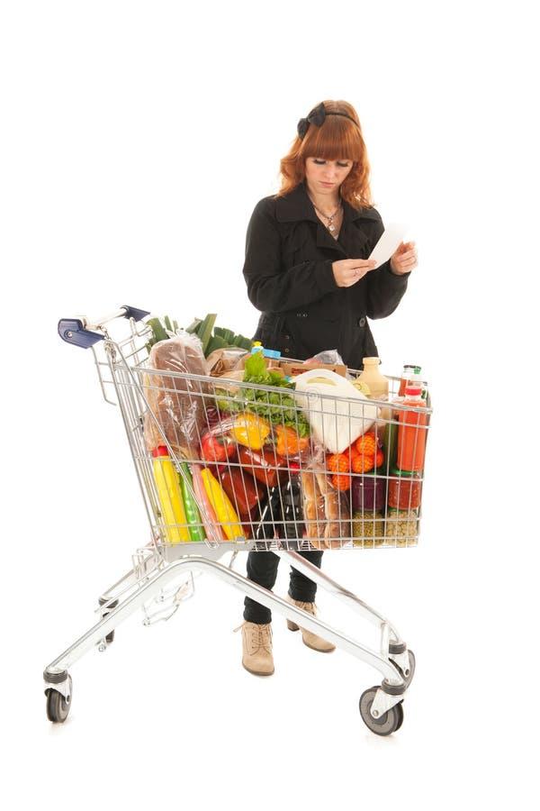 Donna con la lista di acquisto completa della lettura del carrello immagini stock libere da diritti