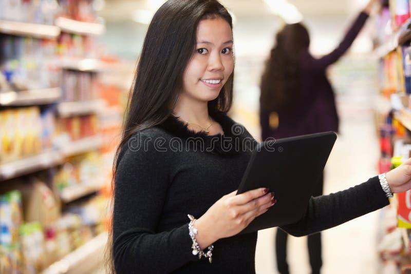 Donna con la lista di acquisto del calcolatore del ridurre in pani immagine stock
