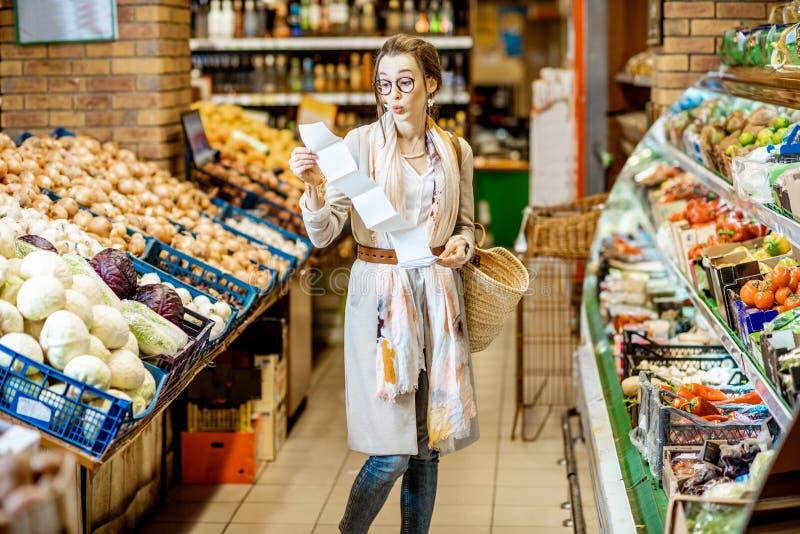 Donna con la lista di compera lunga nel supermercato immagini stock