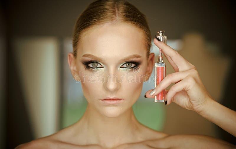 Donna con la lucentezza del labbro, trucco Donna con rossetto, cosmetici Modello di bellezza con lo sguardo di fascino, trucco, v fotografia stock libera da diritti