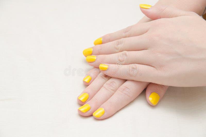 Donna con la lucidatura di unghie gialla fotografia stock libera da diritti