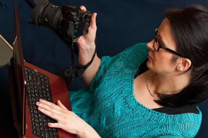Donna con la macchina fotografica ed il computer portatile fotografia stock libera da diritti