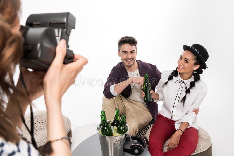 Donna con la macchina fotografica istantanea che fotografa insieme la birra bevente delle giovani coppie felici fotografia stock libera da diritti