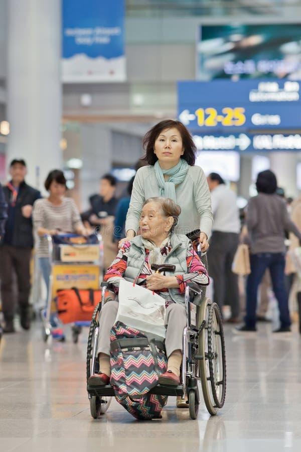 Donna con la madre disabile in una sedia a rotelle all'aeroporto di Icheon, Seoul, Corea del Sud immagine stock libera da diritti