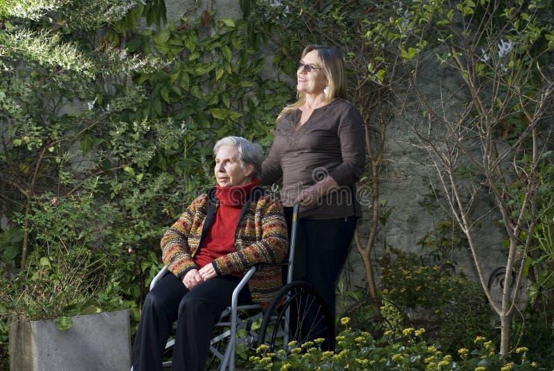 Donna con la madre in giardino - orizzontale fotografia stock libera da diritti
