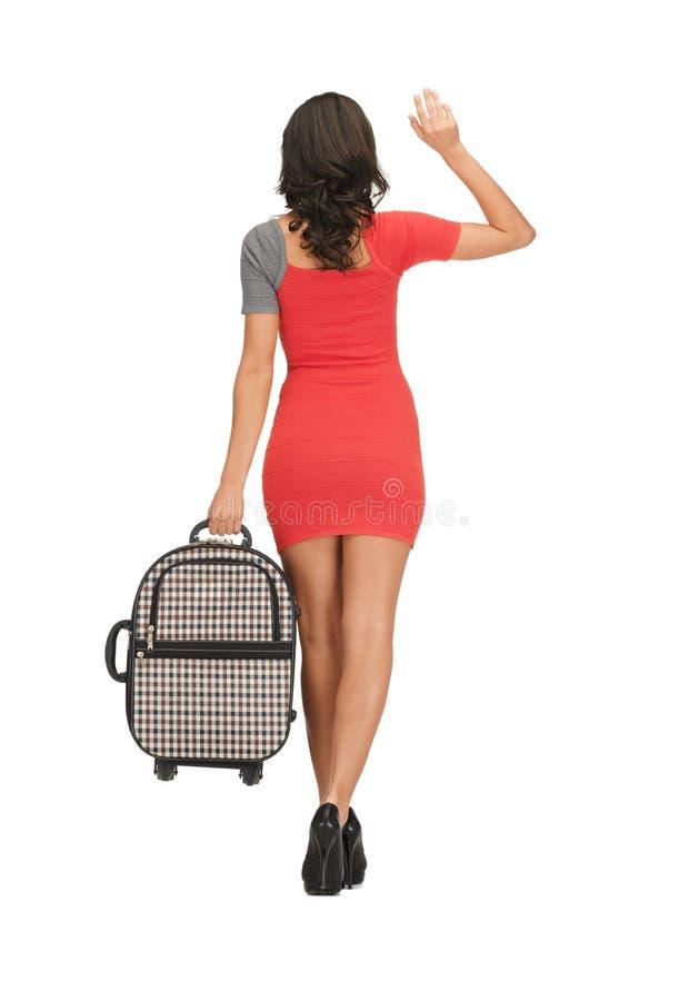 Donna con la mano d'ondeggiamento della valigia immagine stock