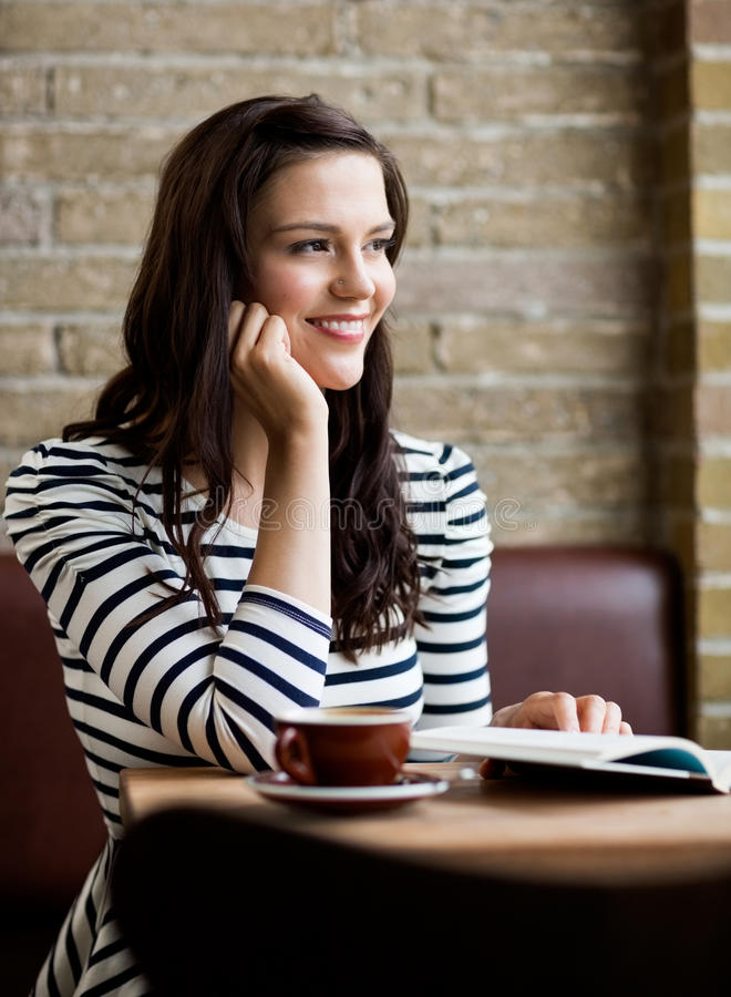 Donna con la mano su Chin Looking Away In Cafeteria fotografia stock libera da diritti