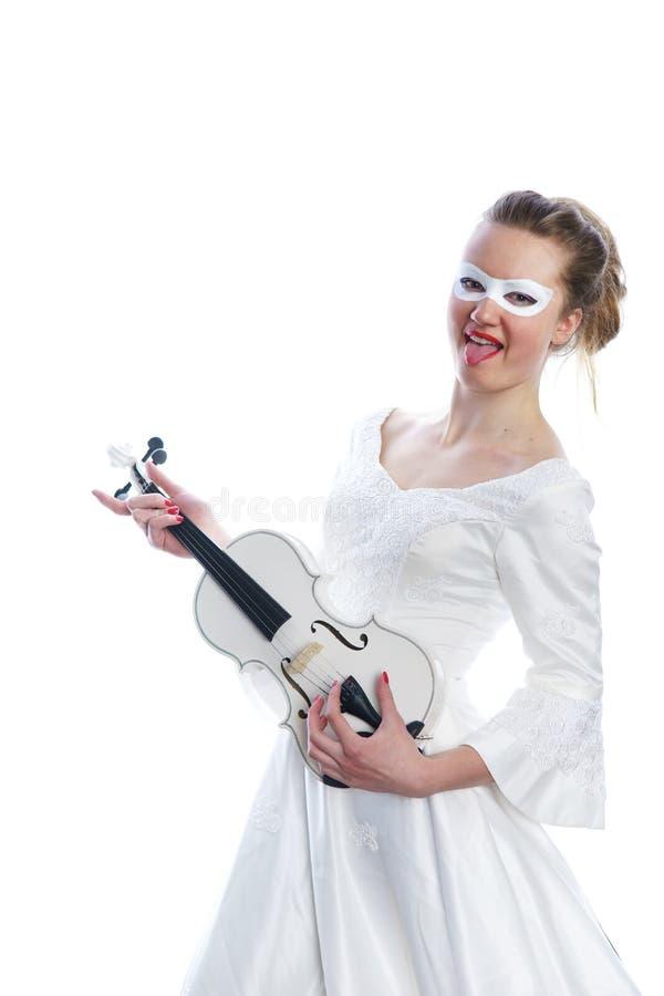 Donna con la maschera bianca del partito sul violino di bianco e del fronte in mani fotografia stock