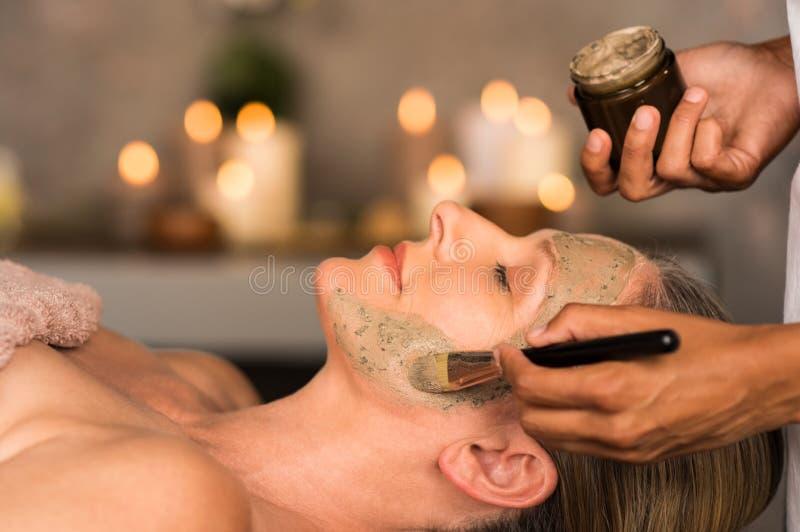 Donna con la maschera dell'argilla sul fronte fotografia stock